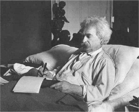 Mark Twain writing in bed.